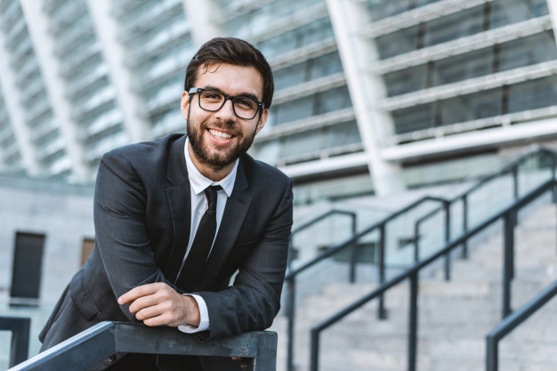 portrait-young-man-businessman-with-eyeglasses-against-background-office-building_2221-2504